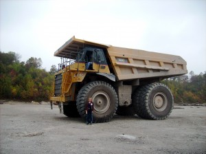 Huge dump trucks haul away the rock, topsoil and waste that become valley fill.  I am standing next to the front tire.