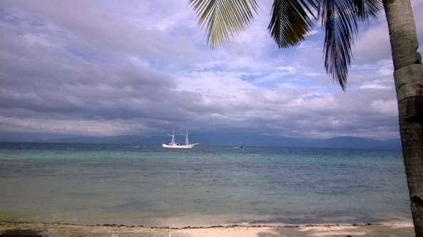 A passing motor yacht, Dacozy Resort beach, Moalboal, Philippines