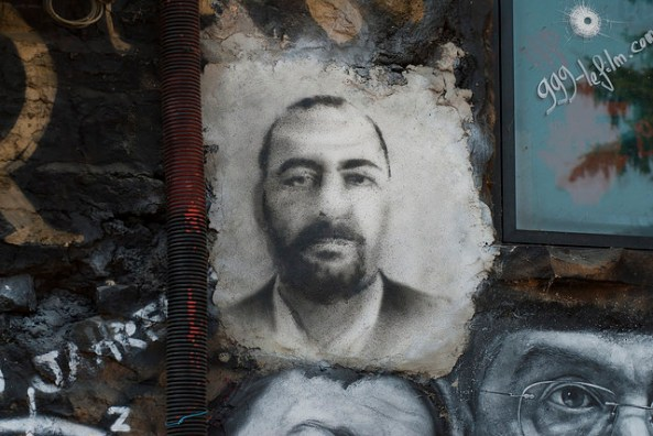 Image on wall of Islamic State chief Abu Bakr al-Baghdadi, beneficiary of misconceived U.S. policies. (Photo: Thierry Ehrmann / Flickr)