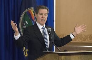 "Governor Sam ""My budget hole is THIS big"" Brownback (image credit: Kansas City Star)"