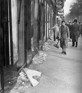 A boy cleans the street after Kristallnacht (10 November 1938)