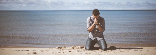 man praying kneeling