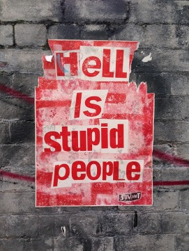 Street art. Torn poster. Hell is stupid people.